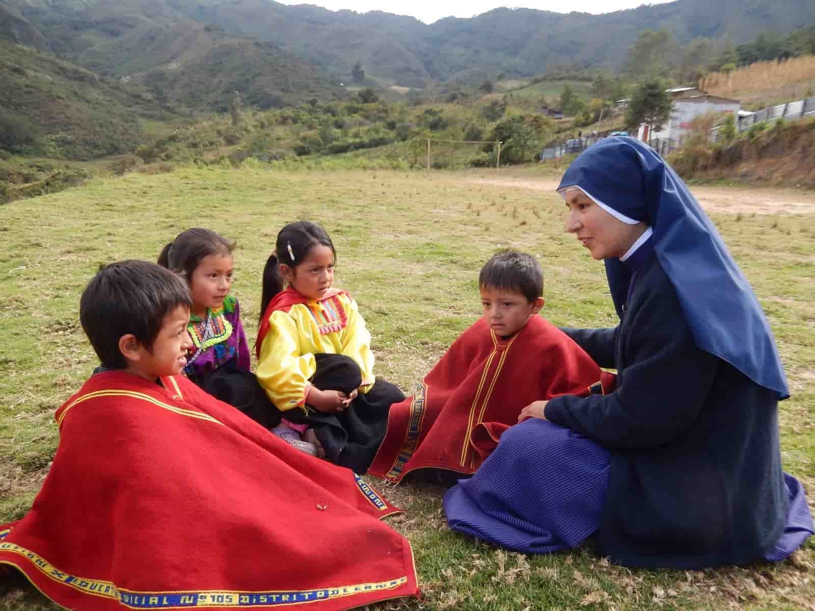 Una misionera de Jesús Verbo y Víctima con unos niños en una zona montañosa