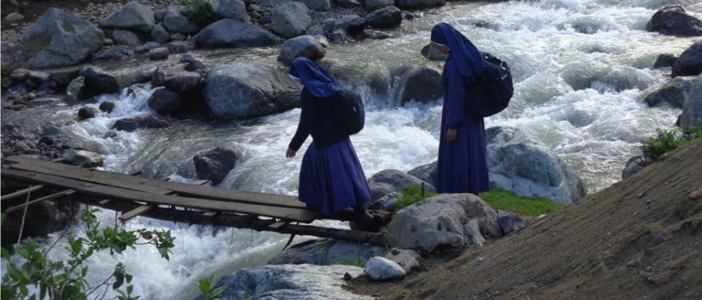 Religiosas Misioneras de Jesús Verbo y Víctima cruzando un río en un puente precario