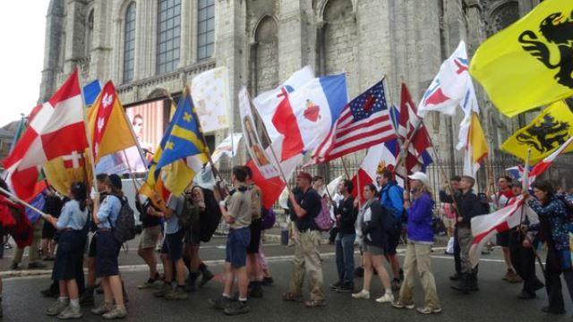 Jóvenes americanos y europeos con banderas del Corazón de Jesús.