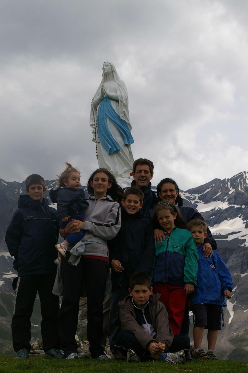 Familia Borsani, junto a una escultura de la Virgen en la montaña.