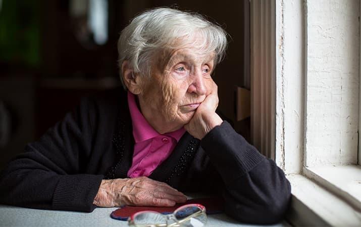Una anciana mira por la ventana en pleno confinamiento