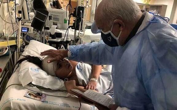 El padre Ángel Camino bendice a Teresita Castillo en el hospital
