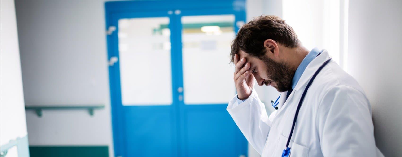 Un médico con bata blanca, deprimido