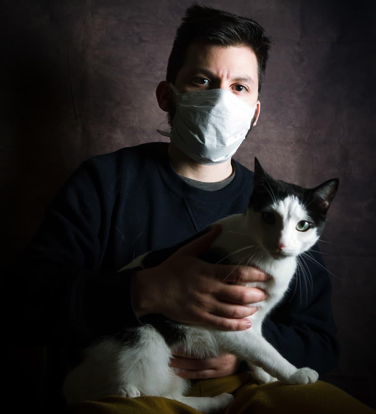 Un hombre con mascarilla y gato