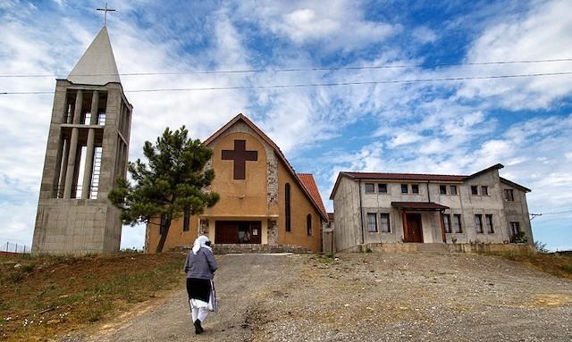 Una mujer camina hacia la iglesia en Dajç (Albania). Foto: Carminemeo.com