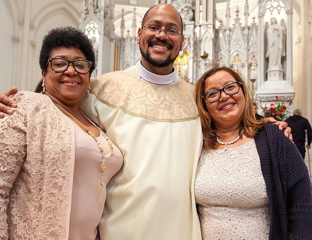 El padre Ángel Miguel abraza a su madre (a su derecha) y a su madrina (a su izquierda) en el día de su ordenación.