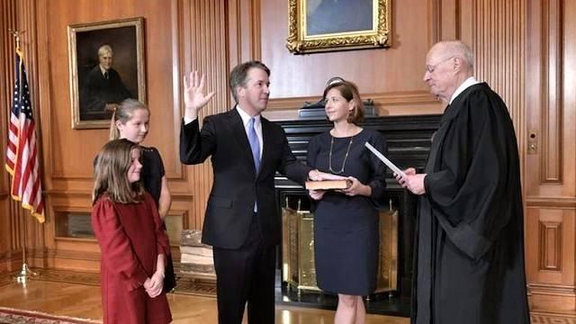 Brett Kavanaugh jura como miembro del Tribunal Supremo ante el juez al que sustituye, Anthony Kennedy, mientras su esposa Ashley sostiene la Biblia. Foto: AP.