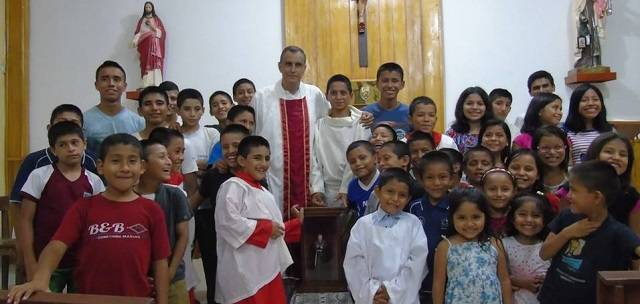 El padre Ignacio María Doñoro con niños del Hogar Nazaret tras recibir la capilla peregrina del Padre Pío llegada desde España
