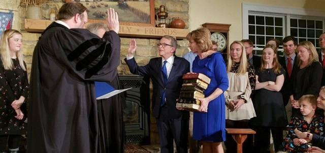 Mike Dewine, jurando el cargo ante su hijo juez de la Corte Suprema de Ohio, y ante las 9 biblias que sujeta su mujer