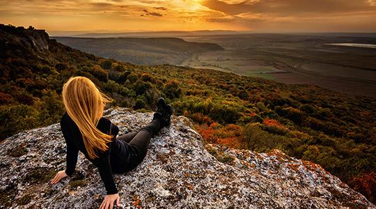 Una mujer contempla el atardecer en un valle desde una loma.
